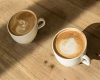 Two cups of frothy coffee sit on a sunlit rustic wooden table