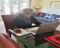 A PAL Volunteer studying on her laptop at home.