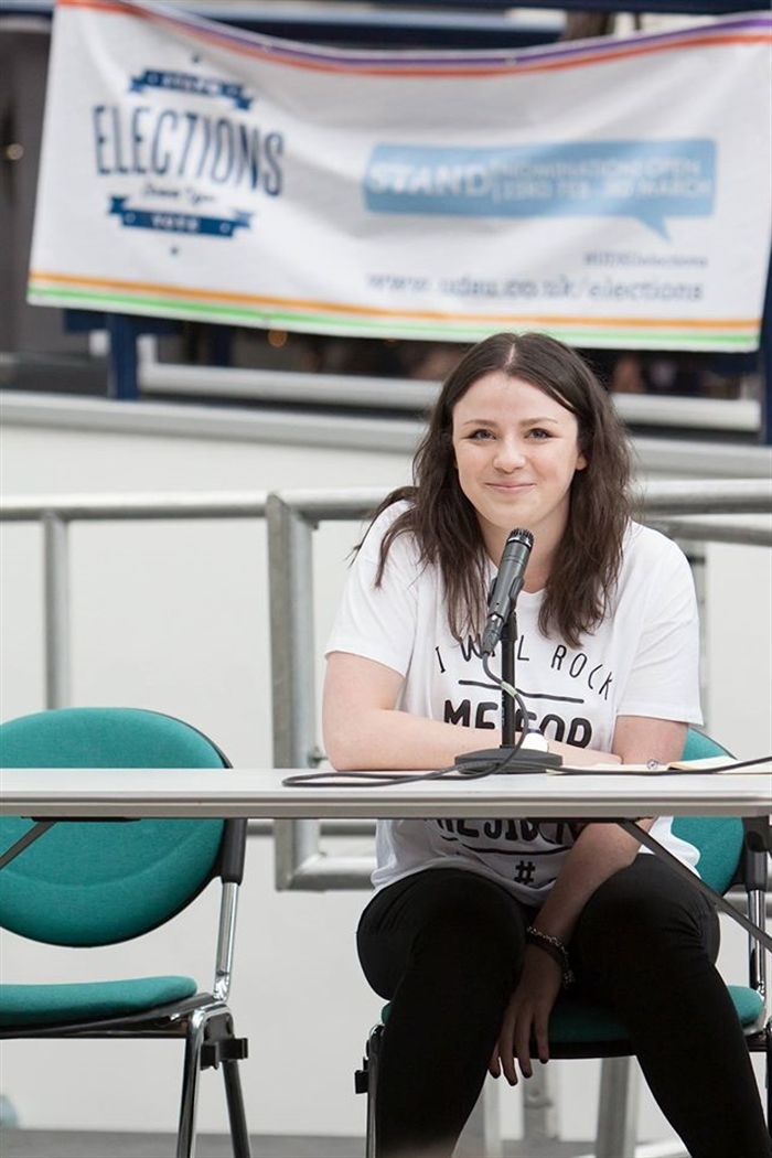 A photograph of Daisy sat at a table during her elections campaign.
