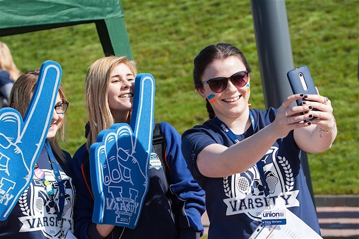 A photo of Daisy at Varsity taking a selfie of herself and students.