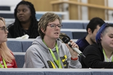 A student representative speaking into a microphone in a lecture theatre