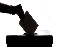 A silhouette of a ballot being cast into a ballot box